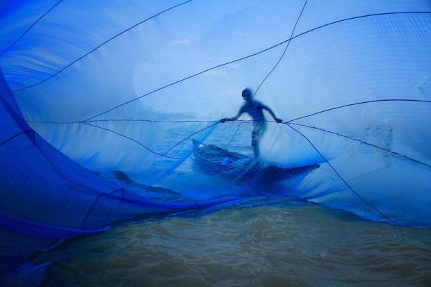 Un pescar din Bangladesh si-a aruncat plasa pentru a prinde prada. Fotografia a fost realizata de Pronob Ghosh. PC: travel.nationalgeographic.com