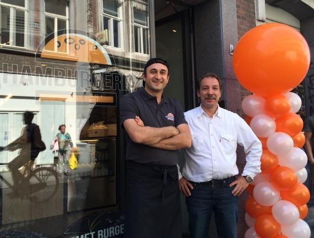 Alex și proprietarul magazinului vecin care a venit să îi felicite la deschidere. PC: Hamburgeria.nl