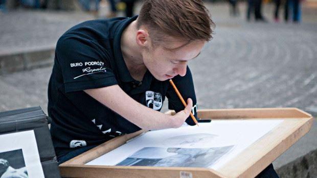 (foto) Emoționant! Un tânăr de 23 de ani pictează, fără mâini, tablouri ce impresionează