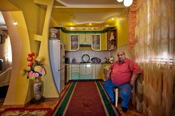 A king in his kitchen, Soroca, Republic of Moldova. The porcelain is on display, as the women in his household still gather with others to cook their dishes along the streets facing their palatial estates. There they cook in big cauldrons, chatting up their children, while their husbands remain home to watch huge television sets till dinner arrives.
