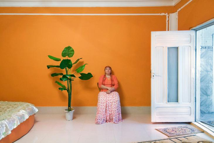 """. This woman, so fond of orange, Ciurea (Iasi), Romania. """"Gypsy Interiors"""" is a collection of portraits capturing the sedate and decorous intimacy of an outwardly loud and gregarious people. Carlo Gianferro has discovered a profound – almost religious – ethnic performance enacted by proud and wealthy Roma deep within their own private quarters;"""