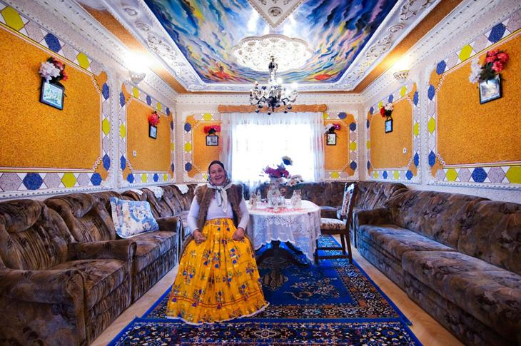 Wife among colours and comfort, Ciurea, Romania. Cheerful colours inviting comfort are essential in the life of Roma, who socialize frequently. Wall to wall sofas presage boisterous gatherings of the clan. Both in furnishings and Roma dress, chromatic combinations are exhibited in vivid pallets -- and sometimes in improbable combinations.