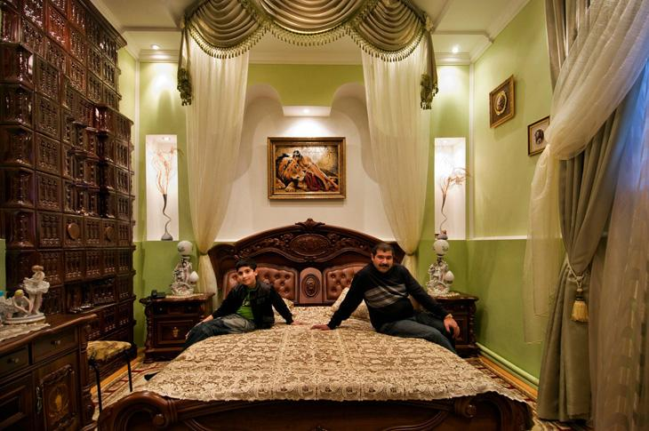Bloodline, symmetry and light combine to illuminate the darkness of a Gypsy Interior, Soroca, Republic of Moldova. Roma patriarchs with mansions in Soroca are often away for extended periods on economic expeditions. Many conduct business in Europe and Russia. Summertime usually signals the return of the Roma fathers to their families.