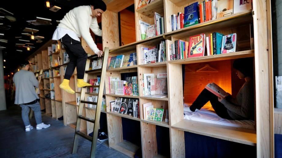 (foto) Într-un hotel-capsulă din Japonia clienții se pot caza printre mii de cărți