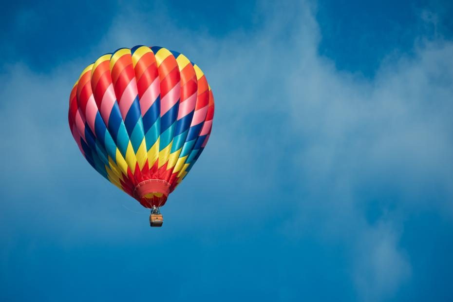 A brightly colored hot air balloon with a sky blue background