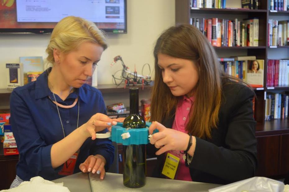 Anastasia Puțuntică voluntară ARC taie o sticlț împreună cu o participantă la un atelier DIY. PC: American Resource Center