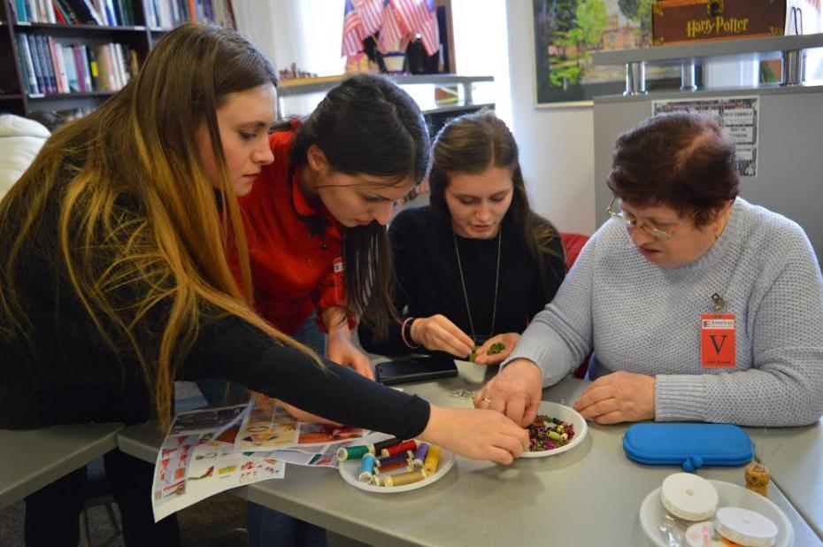 Diana Daicu voluntară ARC la unul din atelierele de creație, la care s-au creat bijuterii împreună cu mame și bunici. PC: American Resource Center