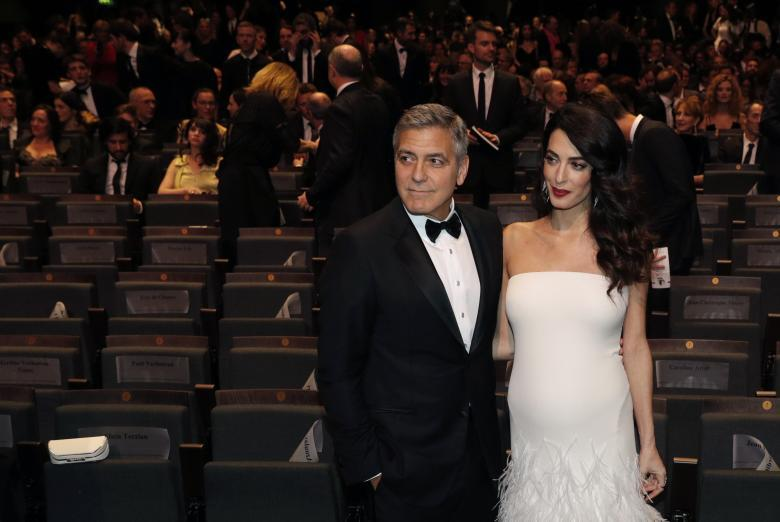 Actor George Clooney and his wife Amal pose before the start of the 42nd Cesar Awards ceremony in Paris. REUTERS/Philippe Wojazer