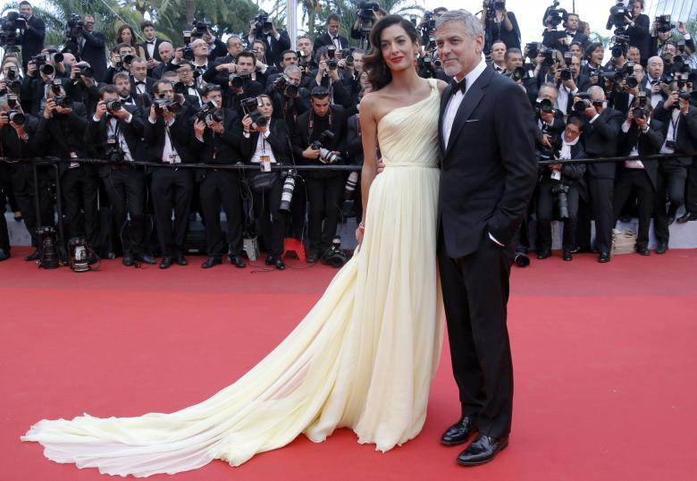 "George Clooney and Amal pose on the red carpet for the screening of the film ""Money Monster"" out of competition at the 69th Cannes Film Festival in Cannes. REUTERS/Regis Duvignau"